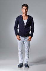 Full length Young man in jeans standing on gray background