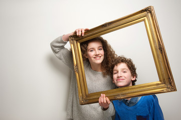 Happy brother and sister holding picture frame