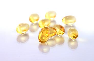 shiny yellow vitamin e fish oil capsule isolated on white backgr