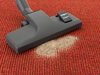 Staubsauger mit Sand auf Teppichboden