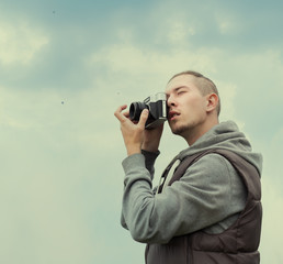 fashionable guy hipster photographer on a cloudy day