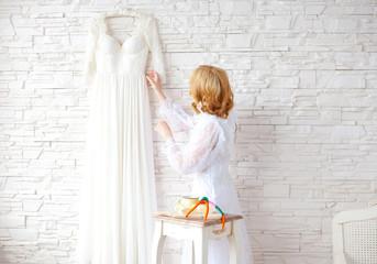 Beautiful blond bride near white brick wall