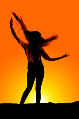 silhouette of woman hair flying arms up