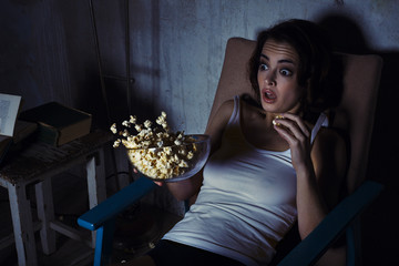 woman, scared horror movie, popcorn drops