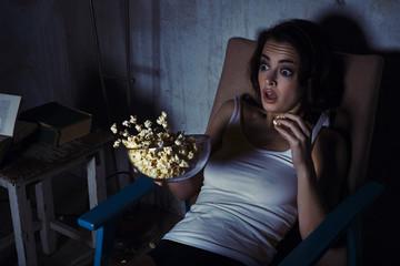 woman, scared horror movie, popcorn drops