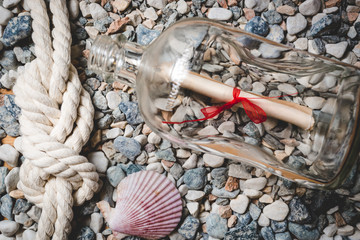 Letter in bottle lying on seashore with rope and seashells