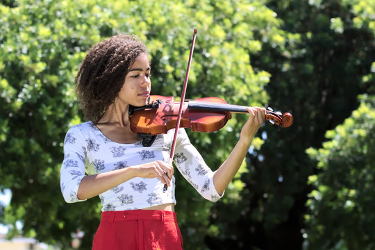 Young woman with curly hair playing violin outdoors