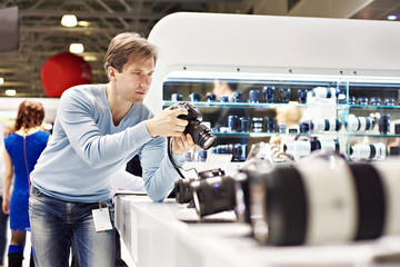 Man photographer tests digital SLR camera in shop