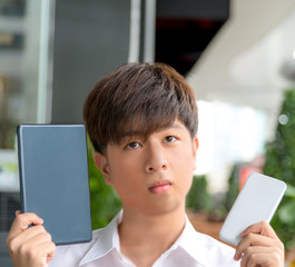 Asian male decide and hesitate to use  smart device tablet