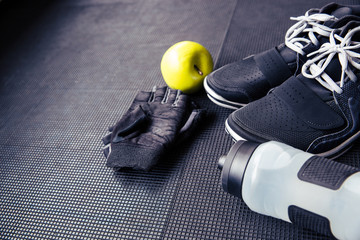 Sports gloves, sneakers, bottle with water and green apple