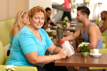 Desperate fat woman in gym holding water bottle