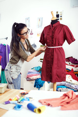 Young female designer measuring dress