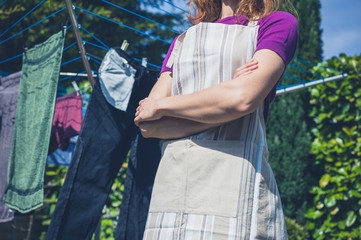 Woman in apron standing by clothes line
