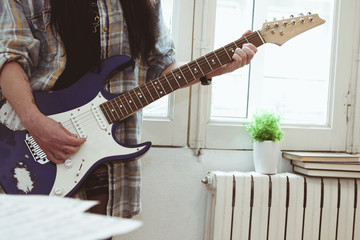 girl playing guitar indoors, lifestyle