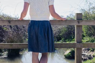Woman standing on small rural bridge