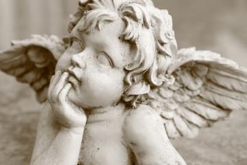 detail of looking up cherub figurine in sepia