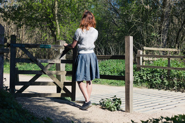 Woman standing by gate in forest
