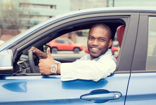 Man happy smiling showing thumbs up driving sport blue car