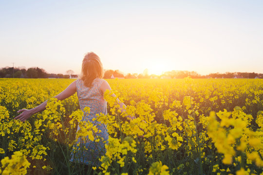 happy young woman enjoing summer in yellow field at sunset