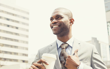 corporate man drinking coffee in sun standing outdoor