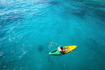 top view of man paddling on kayak in turquoise water