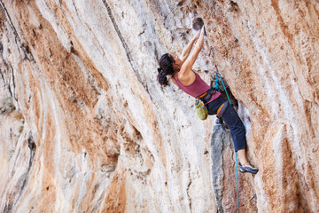 Young female rock climber on overhanging cliff