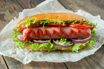 Hot dog with lettuce, tomato and onion