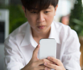 A young Asian boy chat with white smart phone  focused on the de