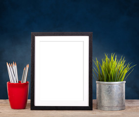 picture frame on blue background with office items and pot plant