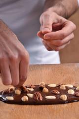 Cocinero preparando barra de chocolate con nueces y almendras.