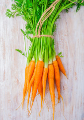 Bunch of fresh carrots on a wooden table