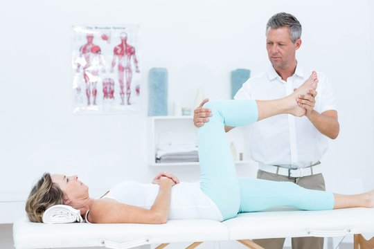 Doctor stretching his patients leg