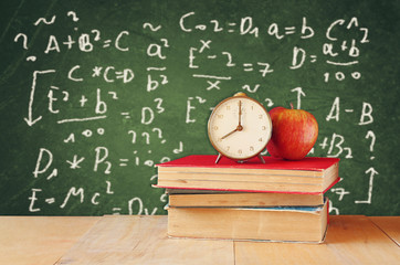 Image of school books on wooden desk, apple and vintage clock o