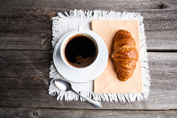 A cup of coffee and a croissant. breakfast table