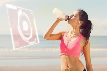 Composite image of beautiful healthy woman drinking on beach