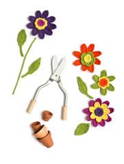 gehäkelte Blumen mit Blumentöpfen und Schere