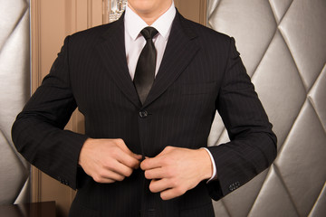 man buttoning his jacket. successful businessman