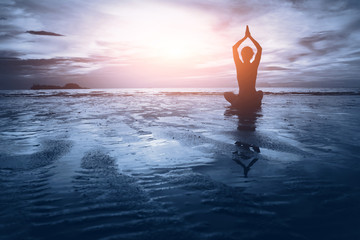 Wall Mural - well being concept, beautiful sunset on the beach, woman practicing yoga