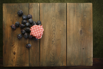 Homemade honey and plums on picnic table