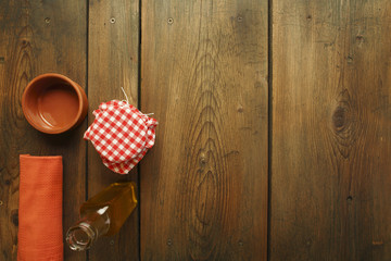 Olive oil, bowl, kitchen towel and jar on picnic table