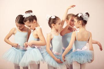 Group of five little ballerinas preparing for performance