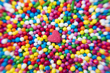 Macro of Sugar Heart over colorfull balls powder background