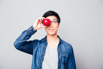 Young asian man covering his eyes with apple