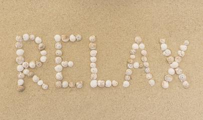 Wort RELAX aus Schneckenhäuschen im Sand