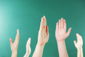 Raised hands on blackboard background in class