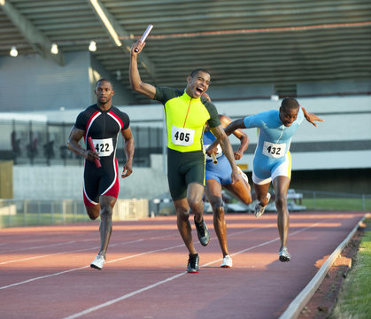 Relay racer crossing finish line on track in race