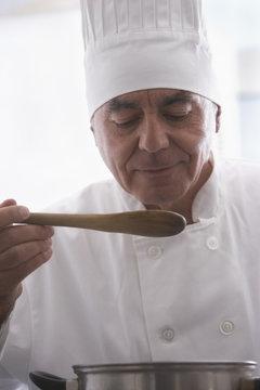 Hispanic chef tasting food in kitchen