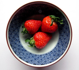 Three strawberries in a blue bowl