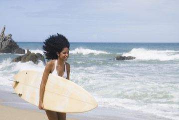 African woman with surfboard at beach