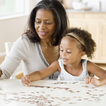 African grandmother helping granddaughter put together a puzzle